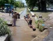 فیصل آباد: نوجوان گرمی کی شدت کم کرنے کے لیے چھوٹی نہر میں نہا رہے ہیں۔