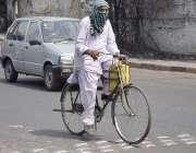 لاہور: ایک سائیکل سوار شہری گرمی کی شدت سے بچنے کے لیے منہ کو کپڑے سے ..