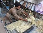 پشاور: محنت کش روم ائیر کولر کی خسیں بنانے میں مصروف ہے۔