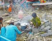 لاہور: خانہ بدوش بچے دریائے راوی کے ساحل پر کھانا پکانے میں مصروف ہیں۔