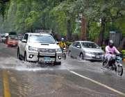 لاہور: موسلا دھار بارش کے بعد جمع شدہ پانی سے گاڑیاں گزر رہی ہیں۔