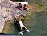 راولپنڈی: نوجوان گرمی کی شدت کم کرنے کے لیے پانی میں جمپ لگا رہے ہیں۔