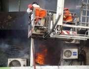 کراچی: ریسکیو اہلکار نجی بینک میں لگنے والی آگ کے بعد امدادی سرگرمیوں ..