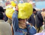 لاہور: خواتین کے عالمی دن کے موقع پر ایک خاتون سر پر سبزیوں بھرا تھیلا ..