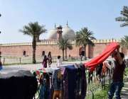 لاہور: ایک نوجوان کپڑے خشک کرنے کے لیے بادشاہی مسجد کے جنگلے پر ڈال ..