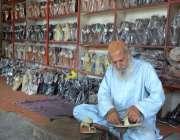 فیصل آباد: معمر محنت کش روایتی انداز سے جوتے بنانے میں مصروف ہے۔