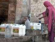 راولپنڈی: خاتون فاٹر فلٹریشن پلانٹ سے پینے کے لیے پانی بھر رہی ہے۔