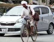 سرگودھا:  ایک شخص  سائیکل پر طارق آباد روڈ پر پانی سے بھرا ہوا روایتی ..