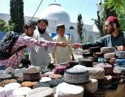 اسلام آباد: رمضان المبارک کے پہلے روزہ کے موقع پر شہری ایک سٹال سے ٹوپیاں ..