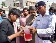 لاڑکانہ: پولیس اہلکار گرمی کی شدت کم کرنے کے لیے مشروف تقسیم کر رہا ..