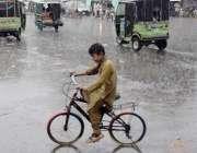لاہور:ایک سائیکل سوار بچہ بارش میں جا رہا ہے۔