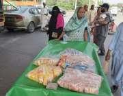 لاہور: ایک بزرگ خاتون ریڑھی پر بچوں کے کھانے کی چیزیں فروخت کررہی ہے۔