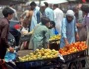 راولپنڈی: دکاندار گاہکوں کو متوجہ کرنے کے لیے فروٹ سجا رہا ہے۔