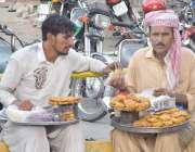 لاہور: نان ٹکی فروخت کرنے والے دو محنت کش آمدن کا حساب کر رہے ہیں۔