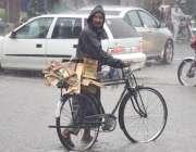 لاہور: ایک شخص شدید بارش میں لکڑی کے کریٹ سیائیکل پر رکھے جا رہا ہے۔