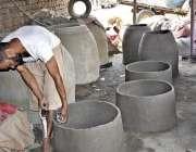 فیصل آباد: کمہار روایتی انداز سے مٹی کے تندور بنا رہا ہے۔