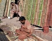 لاہور: محنت کش مختلف اشیاء تیار کرنے کے لیے بانس کاٹ رہا ہے۔
