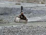 گلگت: ایک معمر شخص مینوئل چیئر لفٹ کے ذریعے دریائے انڈس کراس کررہا ہے۔