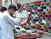 لاہور: شہری سڑک کنارے لگے سٹال سے ٹوپی خرید رہاہے ۔