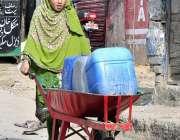اسلام آباد: ایک لڑکی ہتھ ریڑھی پر پینے کے لیے پانی کے کین رکھے لیجا رہی ..