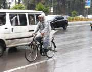 اسلام آباد: سائیکل سوار بارش سے بچنے کے لیے پلاسٹک شیٹ اوڑھے جارہا ہے۔