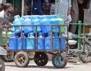 راولپنڈی: محنت کش پینے کے صاف پانی کے کین ہتھ ریڑھی پر رکھے جا رہا ہے۔
