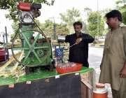 فیصل آباد: شہری سڑک کنارے لگے سٹال سے گنے کا رس پی رہا ہے۔