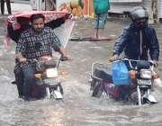 لاہور:ایک شہری بارش کے کھڑی پانی کیوجہ سے بند ہونے والی موٹر سائیکل ..