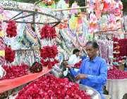 لاڑکانہ: سڑک کنارے ایک دکاندار صارفین کو راغب کرنے کے لئے پھولوں کے ..