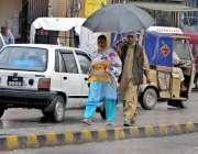 راولپنڈی: شہری چھتری تانے اقبال روڈ سے گزر رہے ہیں۔