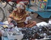 لاہور: ریلوے اسٹیشن کے باہرفٹ پاتھ پر ایک ایک بزرگ محنت کش خاتون عینکیں ..