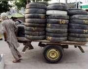 لاہور: مزدور ہتھ ریڑھی پر پرانے ٹائر رکھ کر لے جا رہا ہے۔