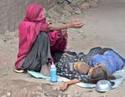 لاہور:ایک خاتون سڑک کنارے بیٹھی بھیک مانگ رہی ہے جبکہ اسکے بچے سو رہے ..