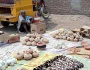 چینیوٹ: سستا بازار میں ایک بوڑھی خواتین مٹی سے بنے ہوئے برتن فروخت کررہی ..