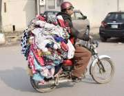 لاہور: ایک موٹر سائیکل سوار لنڈے کے کپڑے فروخت کرنے کے لیے لیجا رہا ..