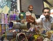 پشاور: عید کی تیاریوں میں مصرو ف دکاندار گاہکوں کو متوجہ کرنے کے لیے ..