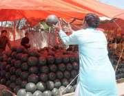 راولپنڈی: محنت کش ٹرک سے تربوز اتار کر فروخت کے لیے سجا رہے ہیں۔