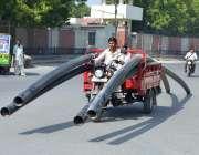 ملتان: پلاسٹک کے پائپوں سے لدے راستے میں ایک لوڈر موٹر رکشہ