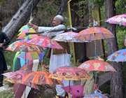 مری: دکاندار نے گاہکوں کو متوجہ کرنے کے لیے چھتریاں سجا رکھی ہیں۔