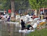 ملتان: محنت کش نہر کنارے خالی تھیلے دھو رہے ہیں۔