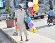 لاہور: ایک محنت کش غبارے اور گیند فروخت کر رہا ہے۔