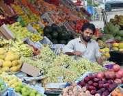 کراچی: ایک دکاندار سڑک کنارے پھل فروخت کر رہا ہے