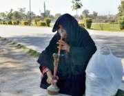 لاہور: ایک معمر خاتون حکہ پی رہی ہے۔