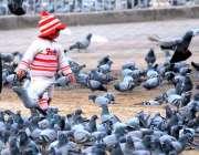 ملتان:چھوٹا بچہ قاسم باغ میں کبوتروں کے ساتھ کھیل رہا ۔