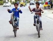 راولپنڈی: بچہ سائیکل پر ون وہیلنگ کرتے ہوئے مری روڈ سے گزر رہا ہے جو ..
