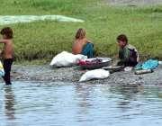 پشاور: خانہ بدوش لڑکیاں دریائے ناگومان کے کنارے کپڑے دھو رہی ہیں۔