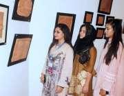 لاہور: الحمراء آرٹ گیلری میں منعقدہ نمائش میں طالبات کی دلچسپی۔