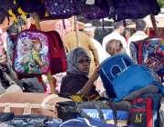 کراچی: صدر کے علاقے میں سڑک  کنارے  ایک خاتون اسکول بیگ  دیکھ رہی ہے