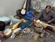 پشاور: کاریگر اپنی ورکشاپ میں رباب بنا رہے ہیں۔