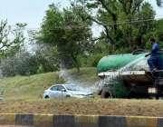 اسلام آباد: سی ڈی اے اہلکار گرین بیلٹ پر لگے گھاس اور پودوں کوپانے لگا ..